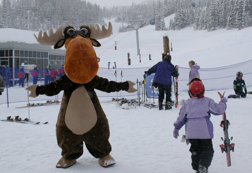 A moose welcomes a young skier to Big Sky Resort, Montana