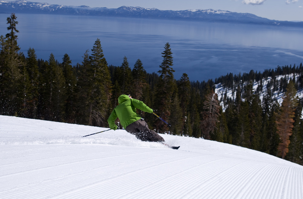 This skier finds a freshly groomed run along with a scenic view of Lake Tahoe at Homewood Mountain Resort, California