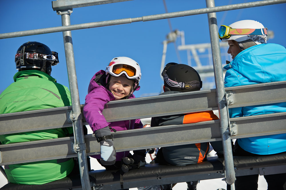 Smiling skiers on Loki Quad. - ©Crystal Mountain