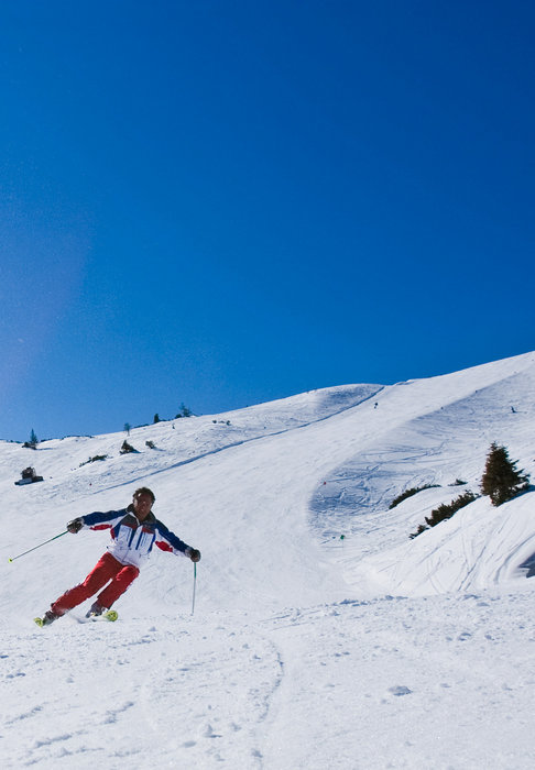 A skier carving down steep slope in Tauplitz.