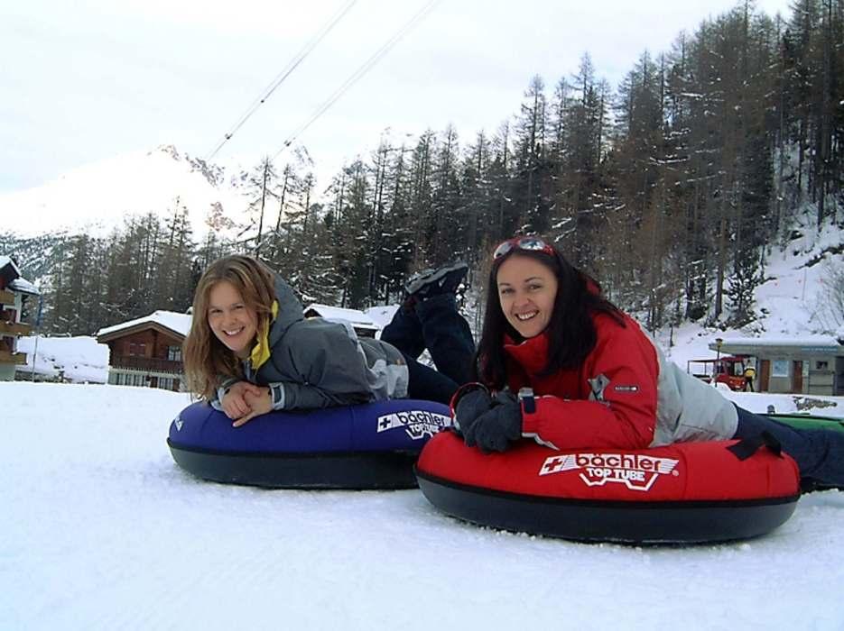 Girls snowtubing in Saas Fee/Saastal, SUI.,