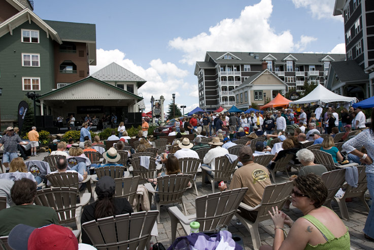 Crowd sitting in square of Snowshoe village