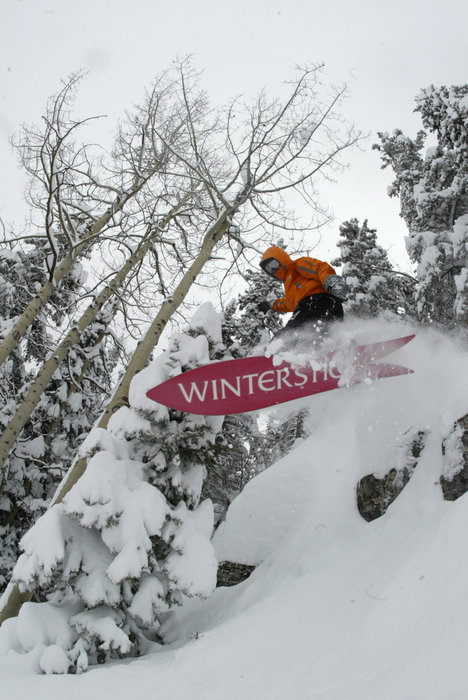 A snowboarder bursting through powder at Durango, CO.