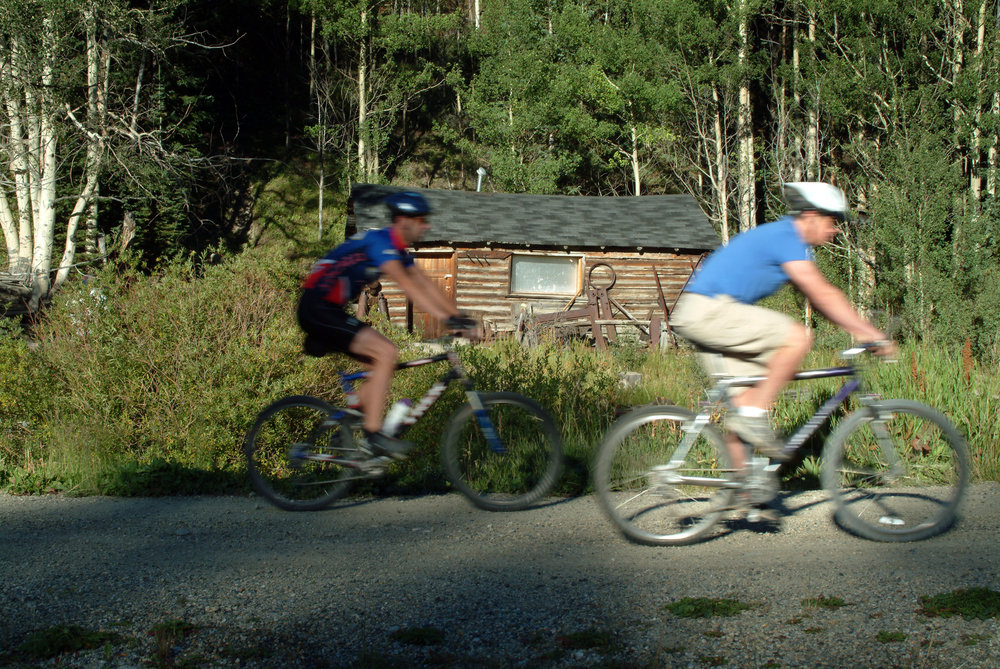 Bikers passing an historic cabin in Breckenridge. Image by Jeff Scroggins.
