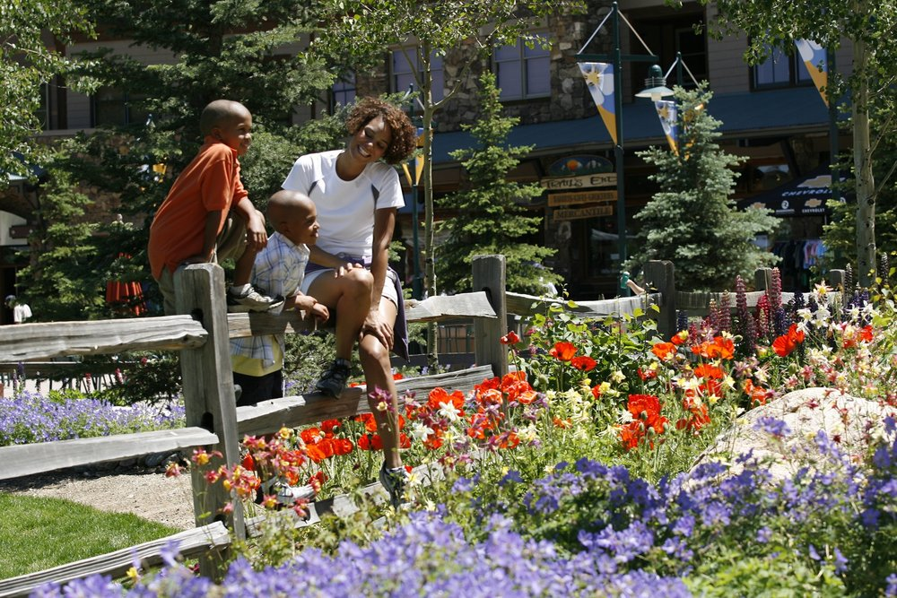 A family pausing near wildflowers in Winter Park, CO.