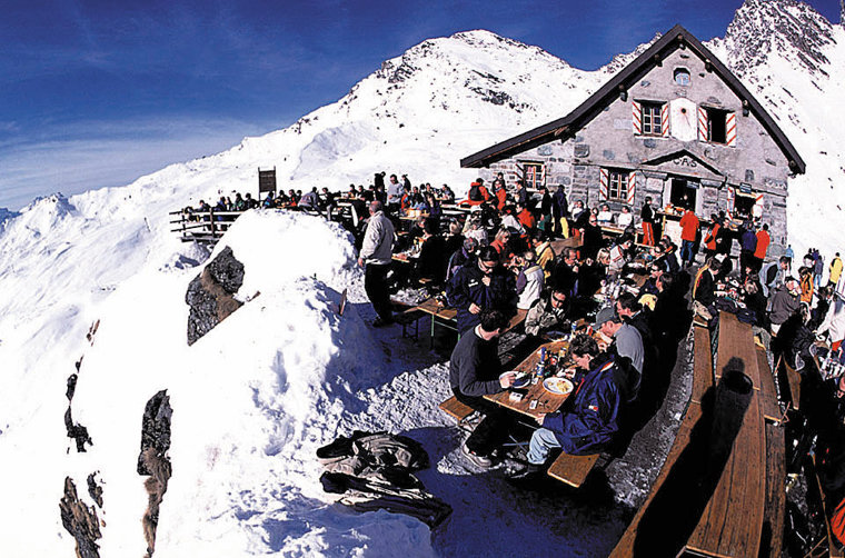 Skiers on sun terrace of mountain restaurant at Verbier