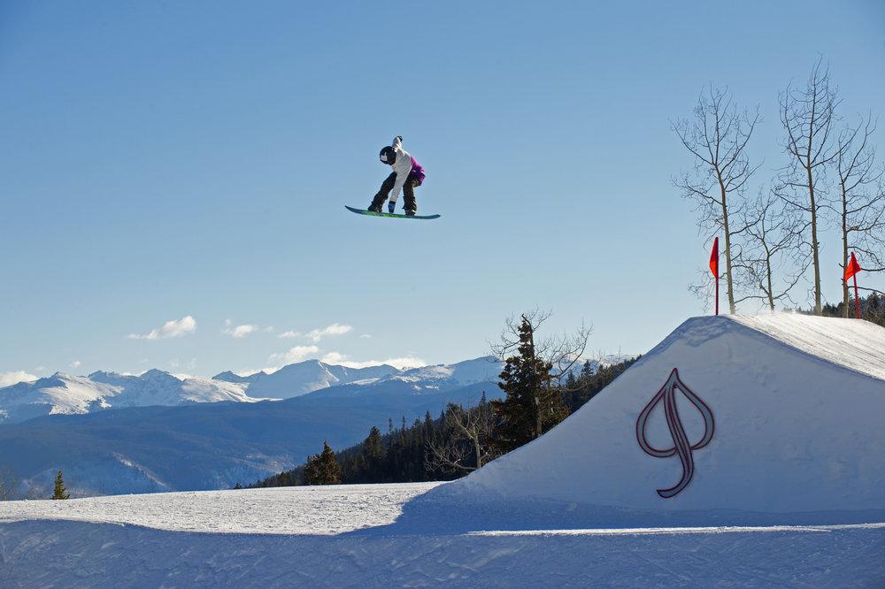 Molly Wilson hitting a jump at Aspen Snowmass on a sunny winter day. - ©Scott Markewitz Photography, Inc.