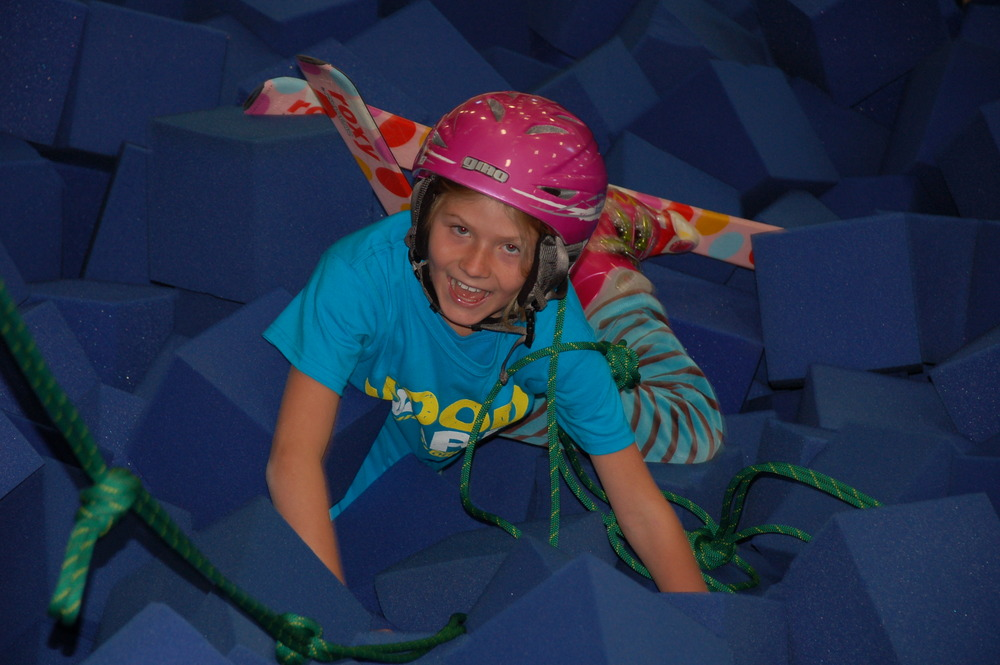 A young female skier climbing out of the Barn's foam pit at Woodward at Copper.