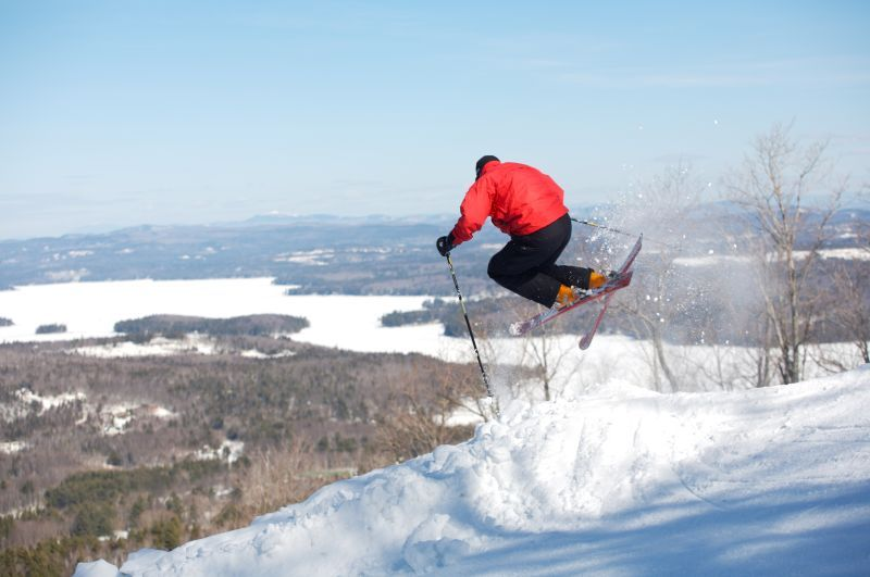 A skier takes flight with Lake Sunapee in the background.