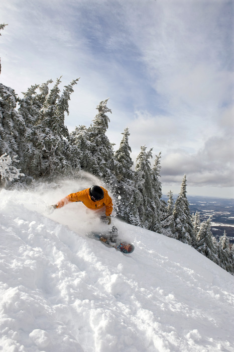 A snowboarder in uneven terrain at Smugglers' Notch, Vermont.