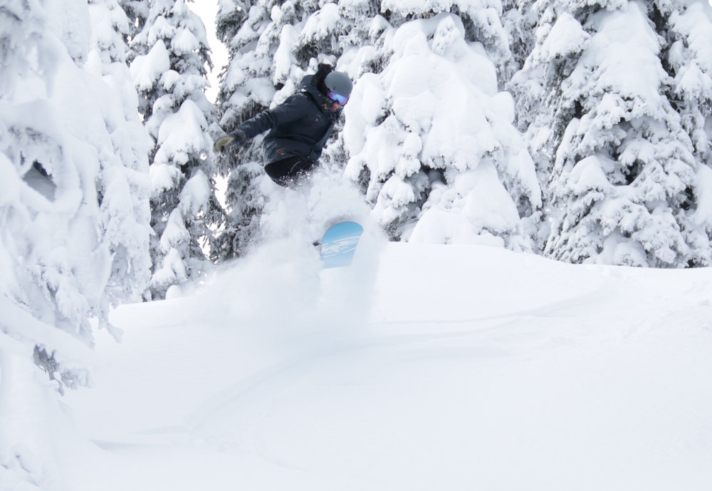 A snowboarder bursts through trees at Whitefish. - ©Chuck Finlay/Whitefish Mtn. Resort