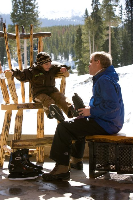A father helping his son on with his skates at Winter Park, CO.