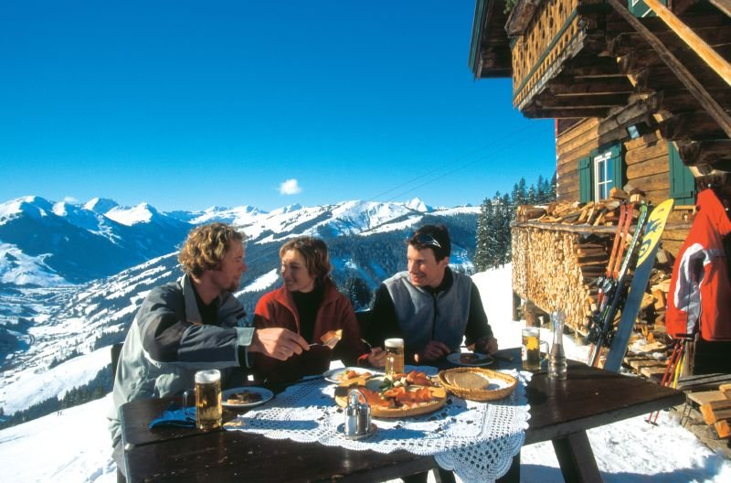 A group rests at the restaurant over Saalbach
