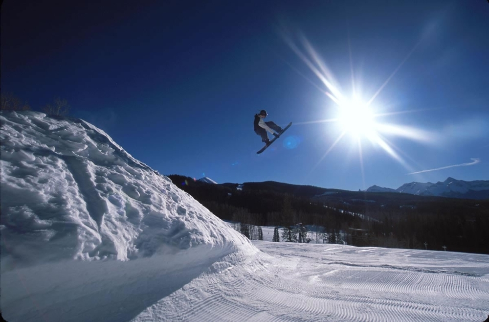 Snowboarder gets elevation in the terrain park in Telluride, Colorado