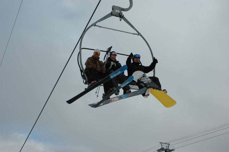 Snowboarders in chairlift, Mammoth, California