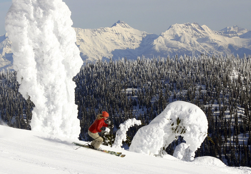 A skier carves by the famous snow ghosts at Whitefish Mountain Resort, with the peaks of Glacier National Park in the distance. Photo: Whitefish Mtn Resort/Brian Schott