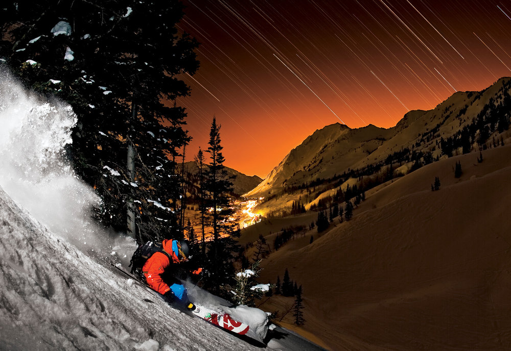 Bryce Phillips skiing powder at night under star trails in the Alta backcountry