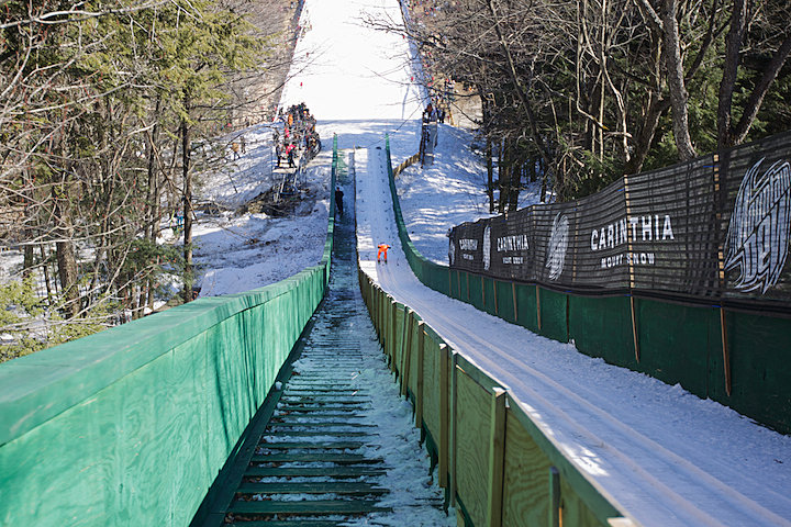 Colton Kissell speeds down the 90 meter ski jump on his way to take off.  Harris Hill is the only 90 meter ski jump in New England.