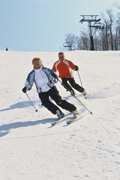 Two skiers cruise down a mountain at Jiminy Peak, Massachusetts