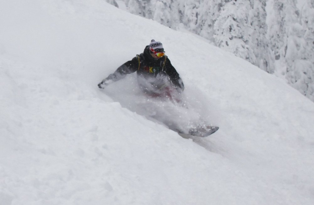 A snowboarder in powder on opening day at Whitefish. Photo courtesy of Whitefish Mountain Resort.