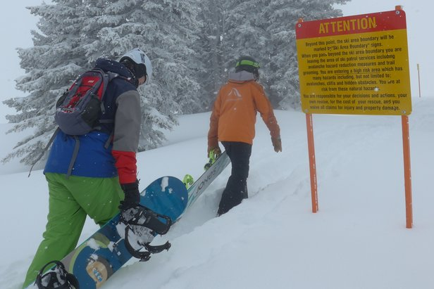 An instructor and snowboarder in the Knowledge is Powder Camp hike to a stash. - ©Mike Hardaker/Mountain Weekly