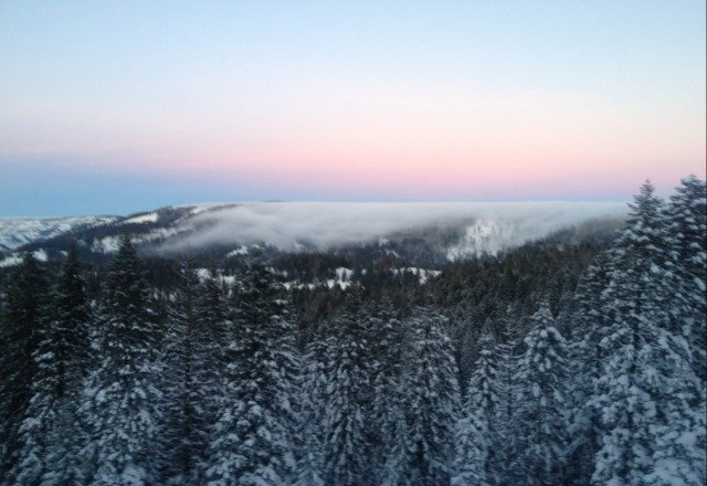 The end of the day view from the top of the mountain. Fog spilling into the valley.