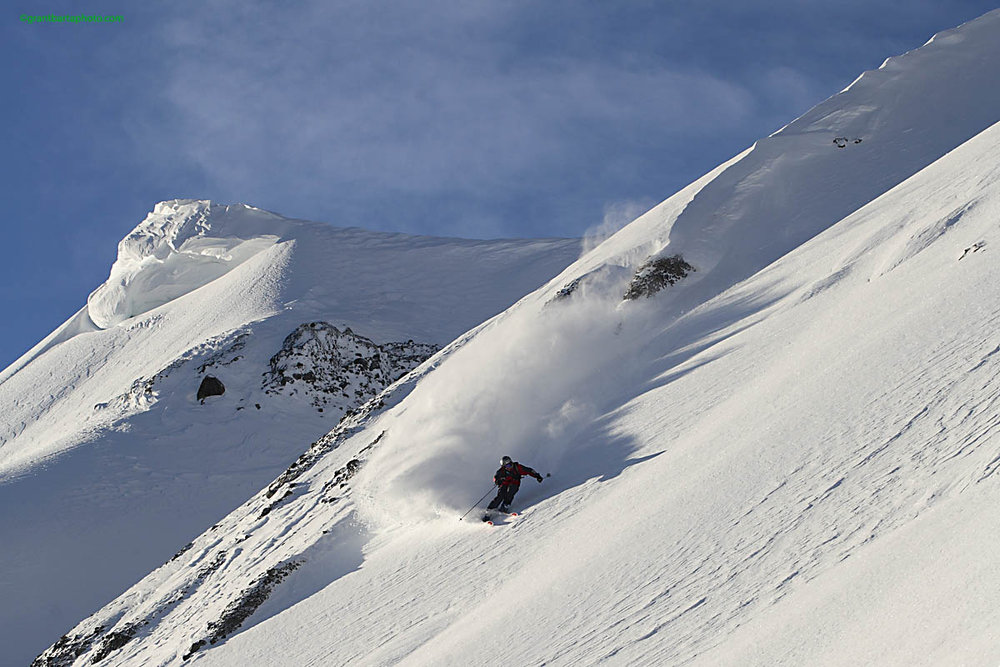 Off-piste skier making fresh tracks on mountainside