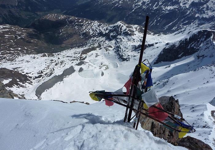 Das Gipfelkreuz des Pizzo Tambo ist mit Gebetsfahnen geschmückt - © Marion Neumann
