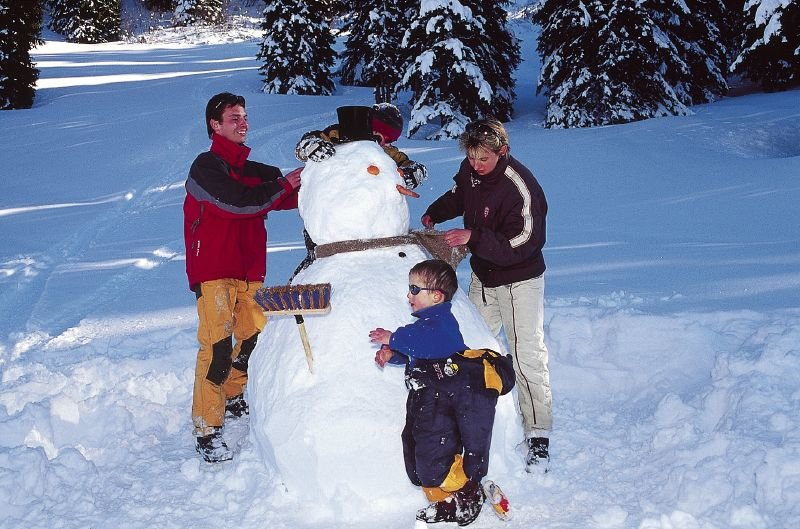 A family building a snowman in Chatel, FRA.