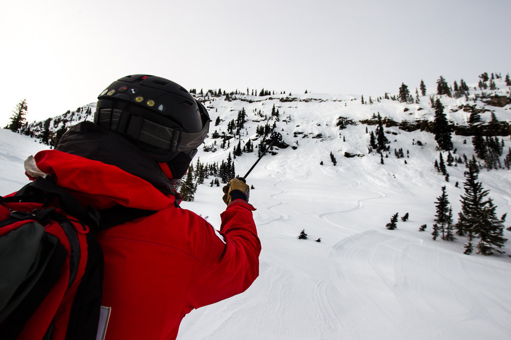 Calder points out small sluff avalanche areas that released after ski cutting. - © Cody Downard Photography