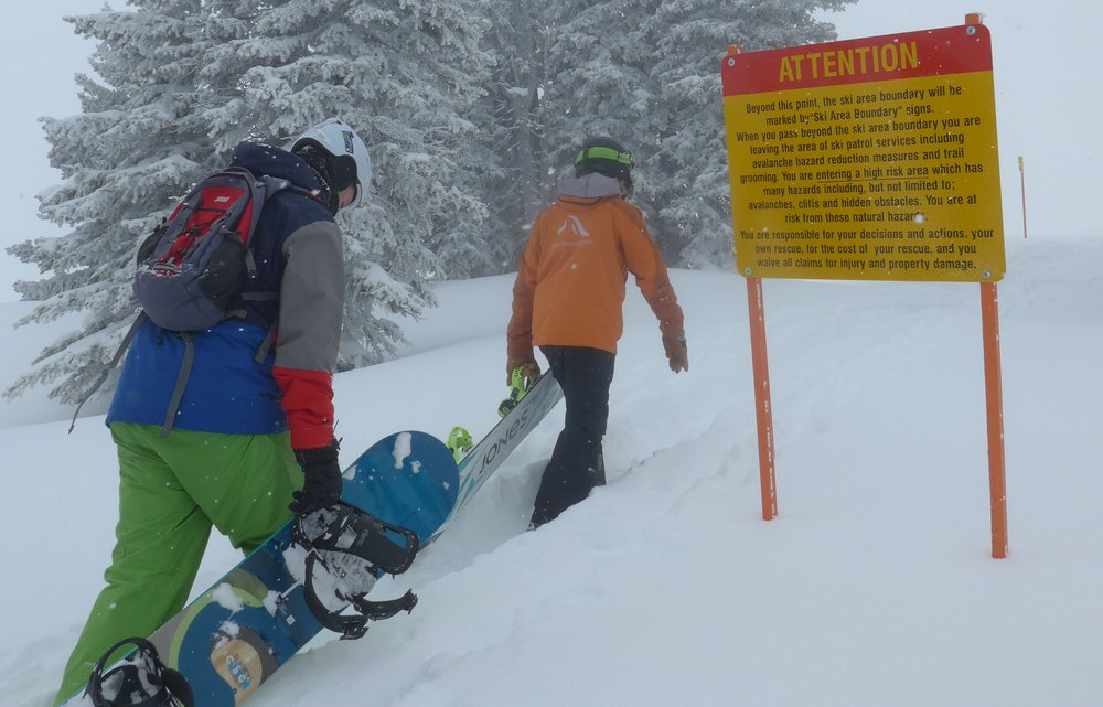 An instructor and snowboarder in the Knowledge is Powder Camp hike to a stash. - © Mike Hardaker/Mountain Weekly