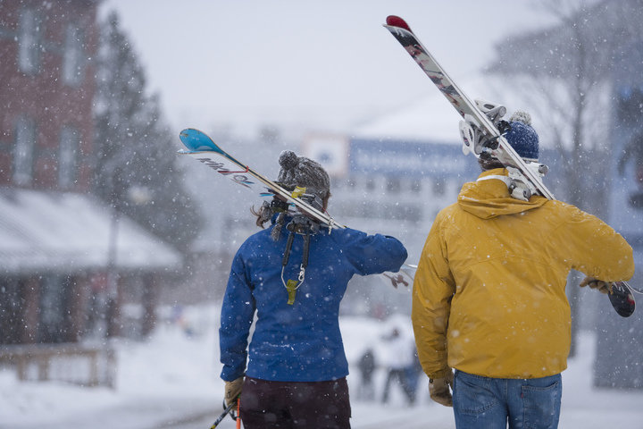 Two skiers stroll through Sugarloaf's village after a day spent chasing early season powder. - © Skye Chalmers