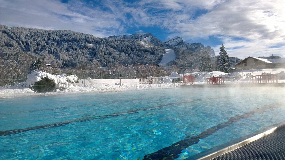 Moment de détente dans l'eau chaude de l'Aquacîme. Bain de soleil face au domaine skiable des Carroz - © Office de Tourisme des Carroz