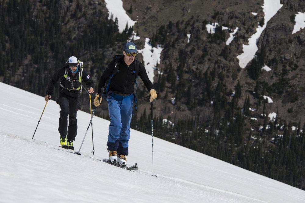 Colorado Mountain School guide, Ian Fowler and Scarpa event coordinator, Joe Risi skin up Sundance for another lap of summer turns. - © Liam Doran