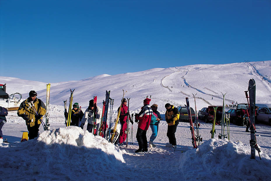 Looking over to a group of skiers gathered outside the ticket office at the Glenshee Ski Centre with the Sunnyside ski run visible behind, northeast of the Spittal of Glenshee - ©P.Tomkins/VisitScotland