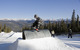 A snowboarder performs a trick off a pipe in Keystone, Colorado's terrain park