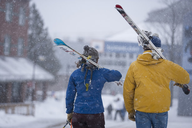 Two skiers stroll through Sugarloaf's village after a day spent chasing early season powder.