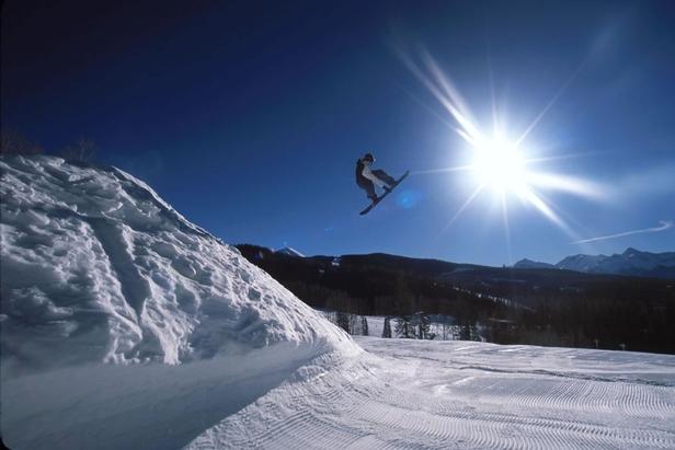 Snowboarder gets elevation in the terrain park in Telluride, Colorado