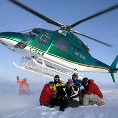 Satisfied customers in front of the chopper at Northern Escape Heli-Skiing. - © Northern Escape Heli-Skiing